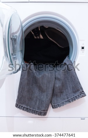 A close up of a washing machine loaded with clothes. Household appliance. - stock photo