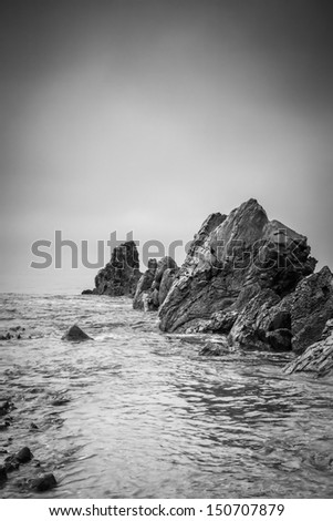 A close up of a wave rushing over rocks on a overcast day in Corona del Mar. - stock photo
