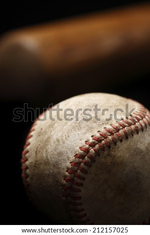 A close-up of a weathered baseball with a bat in the background - stock photo