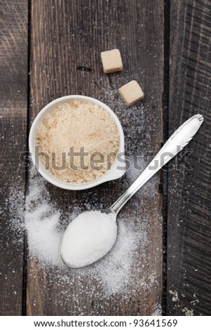A close-up of a white bowl filled with brown sugar. Served on a dark wooden rustic table, with a metal spoon filled with white sugar. Taken directly from above, with brown sugar in focus. - stock photo