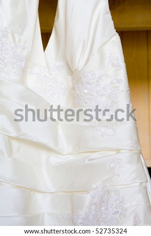 A close-up of a white, hanging, wedding dress.