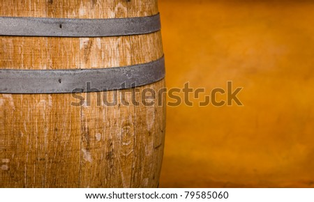 A close up of a wine barrel, with a peach colored wall in the background. - stock photo