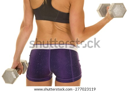 a close up of a woman doing an arm curl. Her back is to the camera. - stock photo