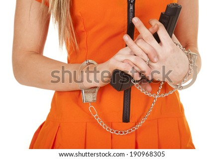 a close up of a woman holding on to a gun with hand cuffs on - stock photo