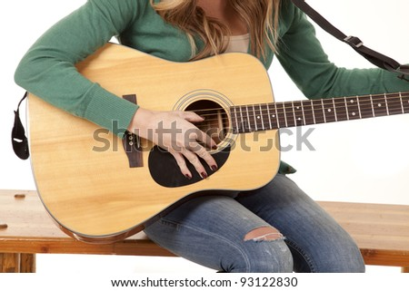 a close up of a woman holding on to her guitar.