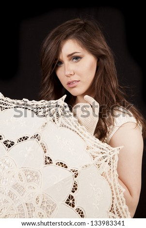 A close up of a woman in her vintage clothing hiding behind her umbrella with a serious expression. - stock photo
