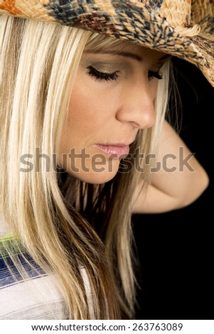 a close up of a woman in her western hat, with a serious expression. - stock photo