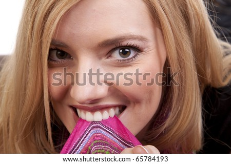 A close up of a woman laying down on a bean bag biting on her colorful scarf. - stock photo