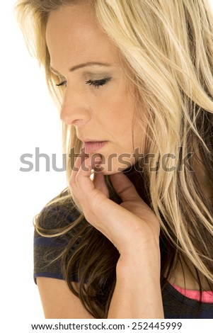 a close up of a woman looking down with her hand on her chin. - stock photo
