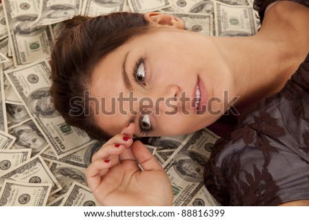 a close up of a woman's face laying in money. - stock photo