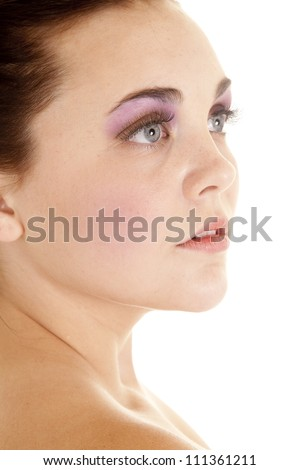 A close up of a woman's face looking to the side with pink eye shadow on her eyes. - stock photo