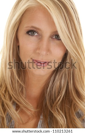 A close up of a woman's face with a small smile playing on her lips - stock photo