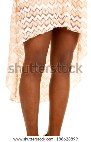 A close up of a woman's legs in her peach dress. - stock photo