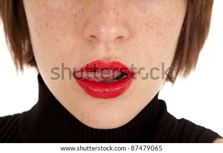 A close up of a woman's mouth showing her licking her lips with her tongue. - stock photo