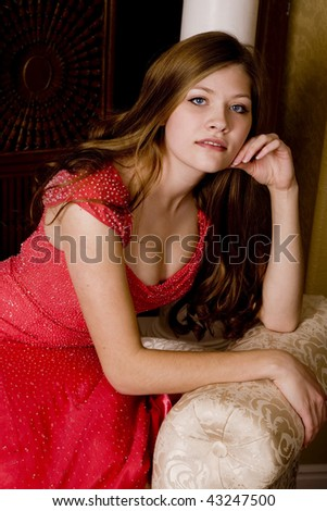 a close up of a woman sitting in her red formal with a sensual look on her face. - stock photo