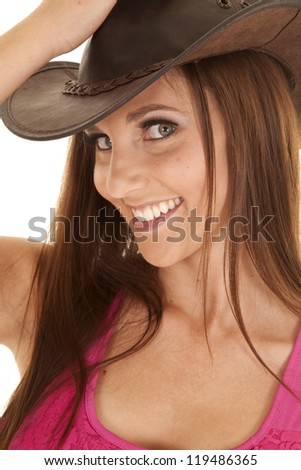 A close up of a woman with a big smile on her lips with her pink tank and cowgirl hat. - stock photo