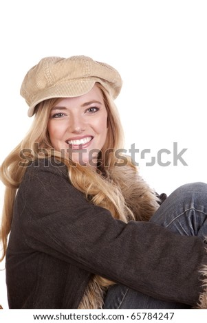 a close up of a woman with a smile while she is wearing a hat and fuzzy coat. - stock photo