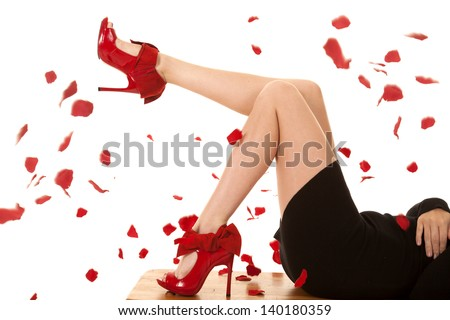 a close up of a woman with her legs up and red shoes with rose petals falling around her. - stock photo