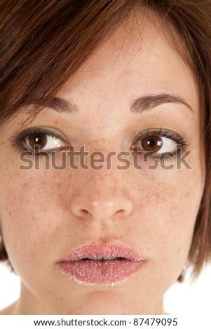 A close up of a woman with sugar on her lips being serious.