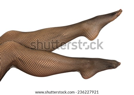 A close up of a womans legs in black fishnet stockings. - stock photo