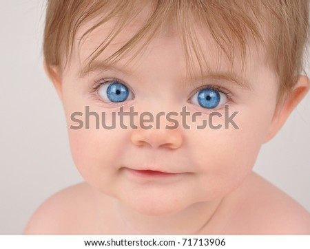 A close up of a young baby with blue eyes staring and posing for the camera.