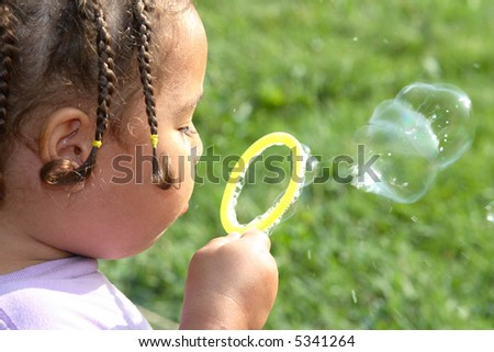A close-up of a young girl blowing soap bubbles - stock photo