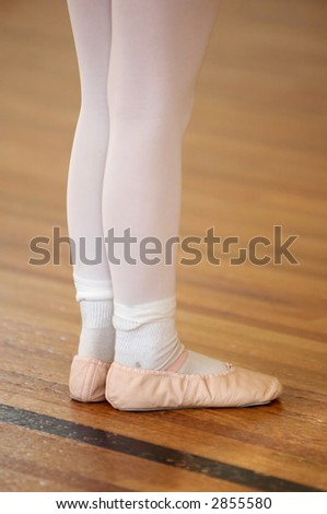 A close-up of a young girl's legs and feet during a ballet class. - stock photo