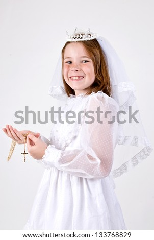 A close-up of a young girl smiling in her First Communion Dress and Veil while holding her rosary beads with a cross.. - stock photo