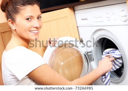 A close up of a young wife putting a cloth into washing machine - stock photo