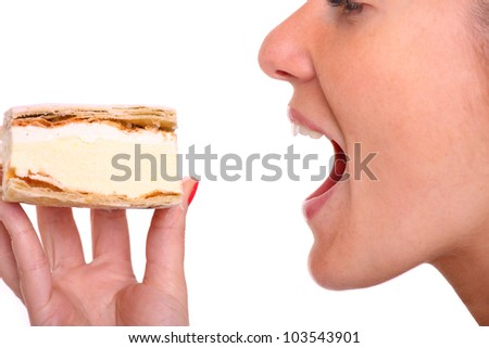 A close up of a young woman eating a cream puff over white background