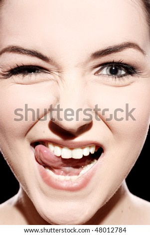 A close up of a young woman pulling a ridiculous face.