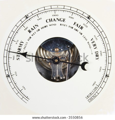 A close up of an aneroid barometer with the dial set to stormy