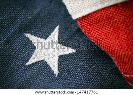 A close up of an antique American flag with a single proud white star on blue with red and white stripes, highly textured