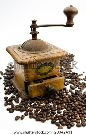 A close up of an antique coffee grinder and coffee beans. - stock photo