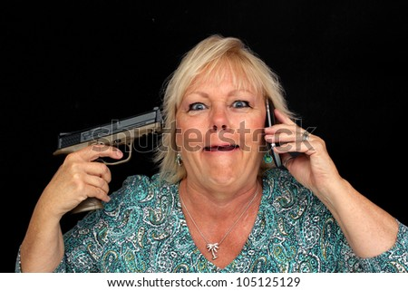 A close-up of an attractive, older blonde woman with a crazed facial expression and pointing a handgun at her ear, holding a cell phone to the opposite ear. - stock photo