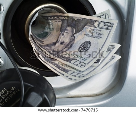 A close up of an automotive gas filler being filled with money - stock photo