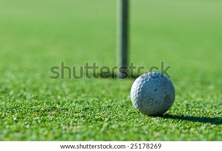 a close up of an old scuffed up golf ball on the green with the hole and flag in the background. Narrow depth of field. - stock photo