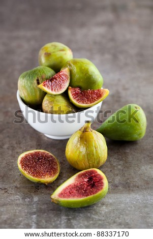 A close-up of assorted fresh figs on a rustic metal surface. - stock photo