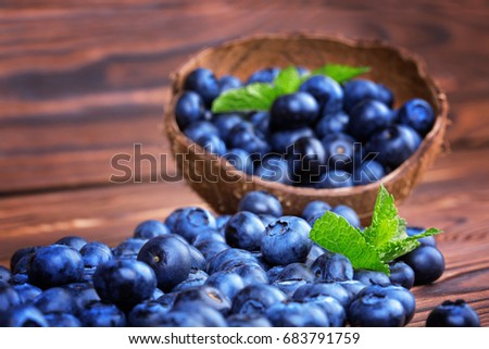A close-up of beautiful and colorful blueberries in a hard coconut shell on a brown wooden background. A group of shiny and juicy blueberries with fresh green leaves. Summer desserts for gourmets.