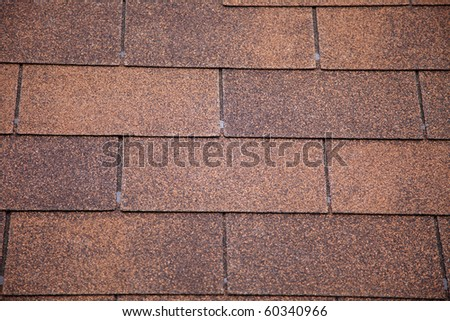 A close-up of brown toned architectural style asphalt roofing shingles. - stock photo