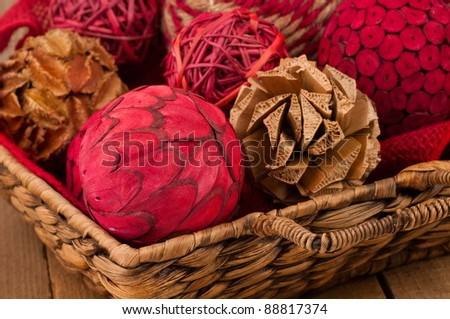 A Close Up of Festive Christmas Ornaments Made of Wood Fibers Arranged in a Wicker Basket and Used as Decoration for the Home with Room for Text or Your Words. - stock photo
