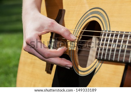A close up of guitar strings and a hand - stock photo