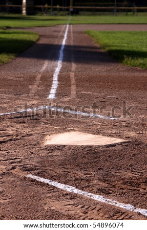 A close-up of home plate and the batters boxes at a baseball field. - stock photo