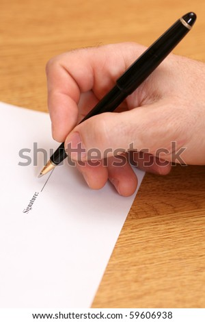A close up of man's hand signing a contract - stock photo
