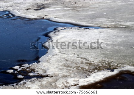 A close-up of melting ice on an Alaskan lake in spring - stock photo