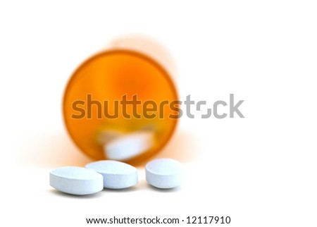 A close up of pills coming out of a bottle on white