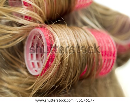 A close-up of red curlers in blond hair - stock photo