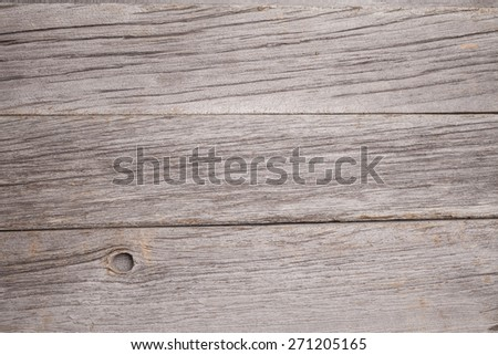 A close up of several planks of aged barn board. A knot is missing from the bottom plank. - stock photo