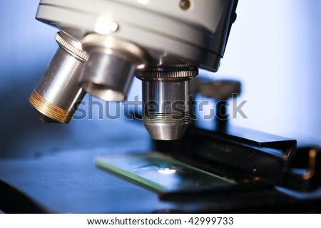 A close up of specimen stage, lenses, and slide of a laboratory microscope ready for examination. - stock photo