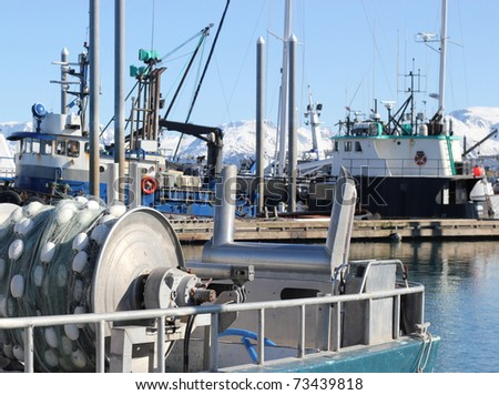 A close up of the back of a fishing boat with a net reel in the harbor with other boats in the background - stock photo
